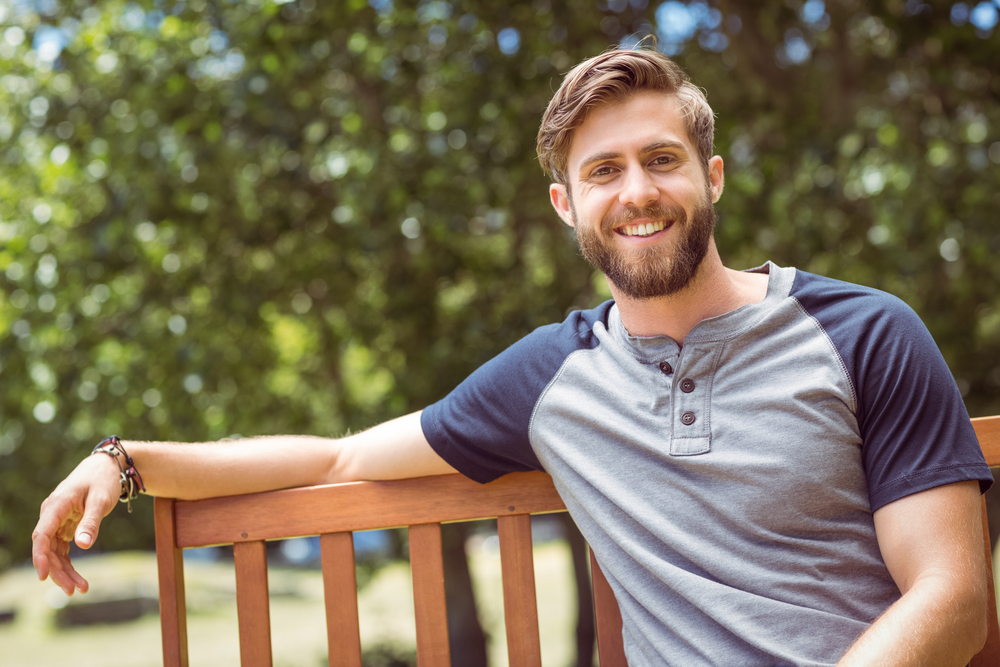 Young man relaxing on park bench on a summers day-3